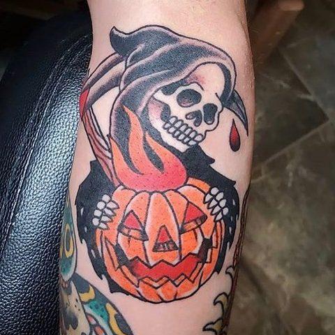 Tattoo of grim reaper with a pumpkin